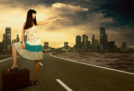 Young woman waiting on the road with her vintage baggage photo