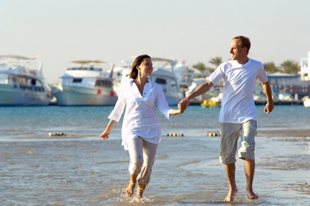 yacht people: View of happy young couple walking on the beach, holding hands.
