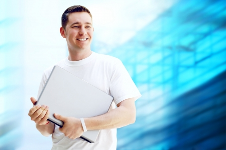 Young happy man or student with laptop and phone on the business background photo