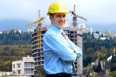Young architect wearing a protective helmet standing on the mountains building outdoor background photo
