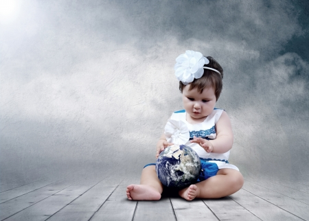 Child sitting with globes in hands photo
