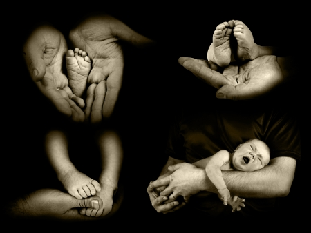 Babys foots in father hands on the monochrome background photo