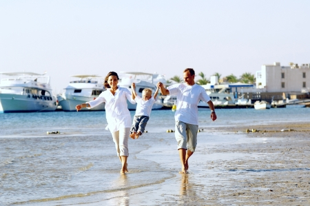 yacht people: View of happy young family having fun on the beach
