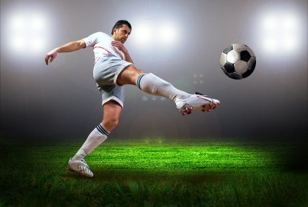 footballer: Happiness football player after goal on the field of stadium with light