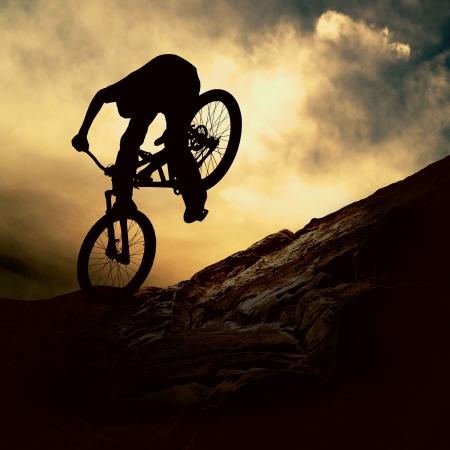 bike race: Silhouette of a man on muontain-bike, sunset Stock Photo