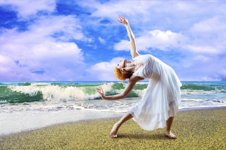 Woman dancer posing on the beach photo