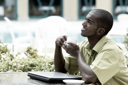 Young happy man or student with laptop sitting at the table  Stock Photo - 15648569