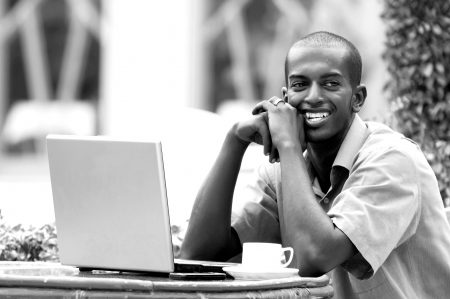 Young happy man or student with laptop sitting at the table Stock Photo - 15692373