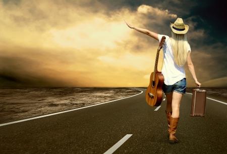 Jonge vrouw met gitaar op de weg en haar vintage bagage
