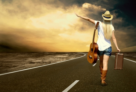 country highway: Young woman with guitar on the road and her vintage baggage