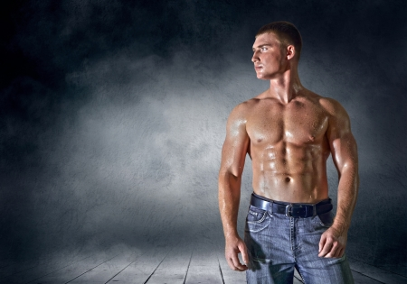 naked male body: Bodybuilder posing on the outdoor grunge background