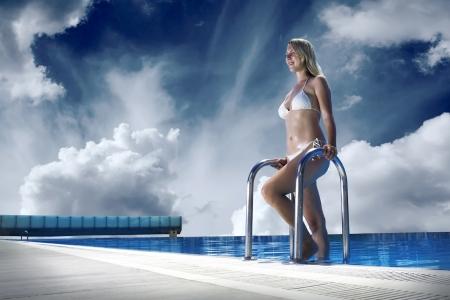 stay beautiful: Beautiful happiness girl in white bikini stay near the waterpool Stock Photo
