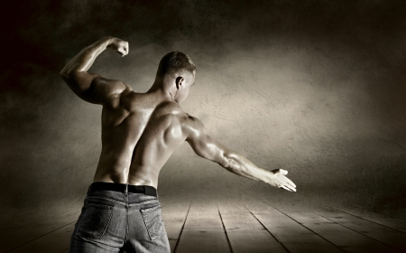 arm muscles: Bodybuilder posing on the outdoor grunge background