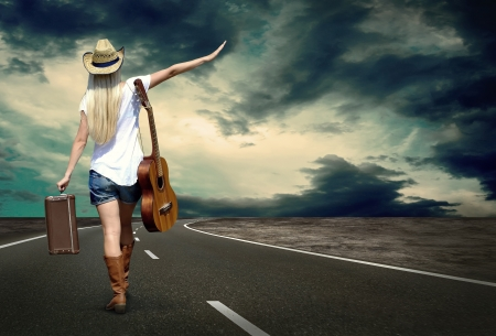 country music: Young woman with guitar on the road and her vintage baggage