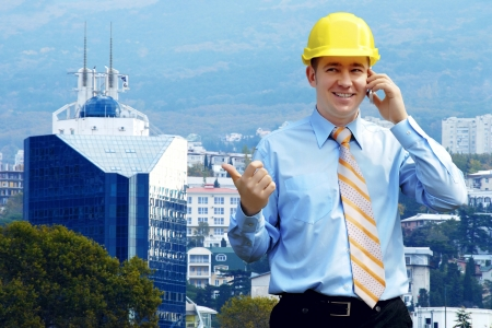 industry park: Young architect wearing a protective helmet standing on the mountains building outdoor background