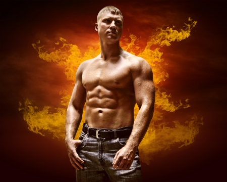 muscular build: Bodybuilder posing on the fire flames background