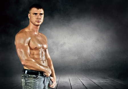 pectoral: Bodybuilder posing on the outdoor grunge background