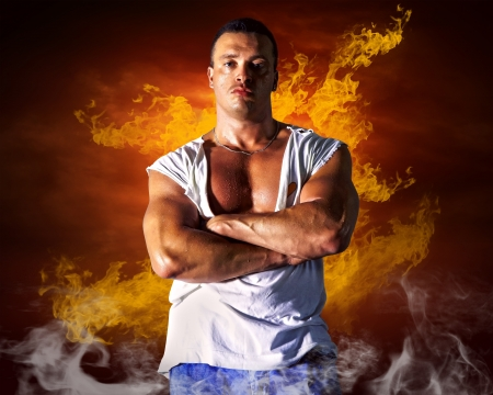 Bodybuilder posing on the fire flames background Stock Photo - 16669782