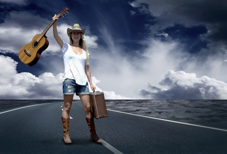 street musician: Young woman with guitar on the road and her vintage baggage