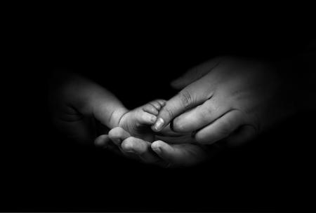 manos y pies: Foots Babys en las manos del padre en el fondo monocromo