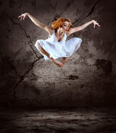 Woman dancer jump posing on background  photo