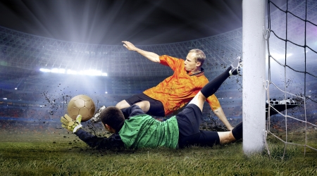 football fan: Football player and jump of goalkeeper on the field of stadium at night