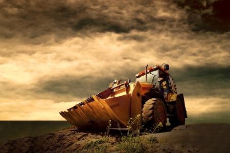 Yellow tractor on golden sunrise sky