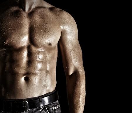 muskelaufbau: Bodybuilder posiert auf dem schwarzen Hintergrund