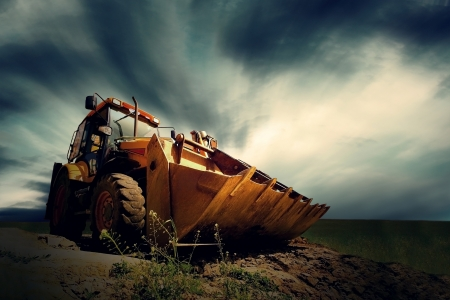 'earth mover': Yellow tractor on sky background