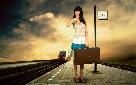 Girl waiting train on the platform of railway station photo