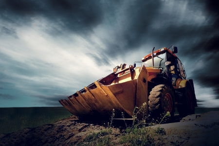 gold shovel: Yellow tractor on sky background
