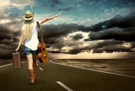 Young woman with guitar on the road and her vintage baggage photo