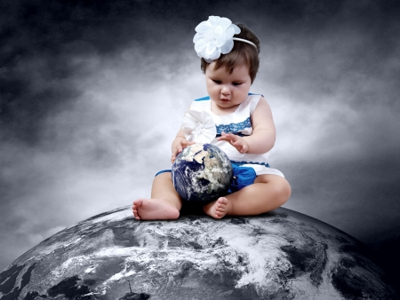 Child sitting on the Planet Earth with globes in hands photo