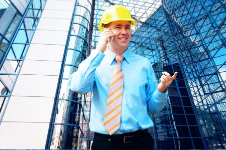 construction site helmet: Young architect wearing a protective helmet standing on the building background Stock Photo