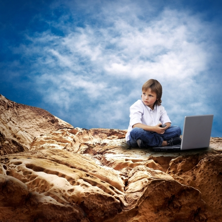 Child with laptop on the mauntain under sky with clouds Stock Photo