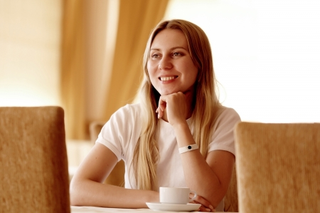Happy woman in white with cup of coffee or tea  photo