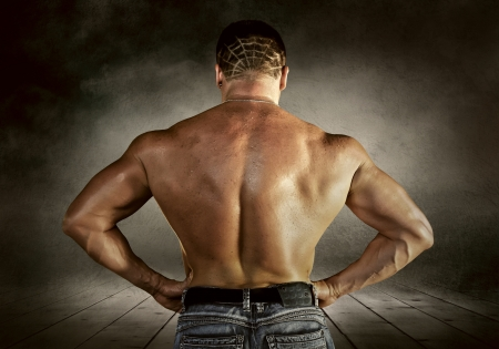 Bodybuilder posing on the outdoor grunge background photo