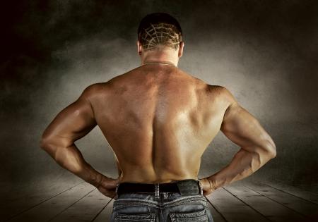 muscular build: Bodybuilder posing on the outdoor grunge background