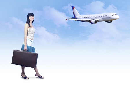 Young woman on the vintage baggage wait on the flying photo