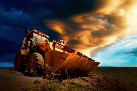 golden shovel: Yellow tractor on sky background