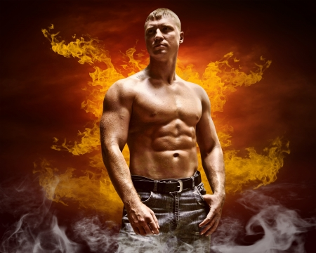 Bodybuilder posing on the fire flames background photo
