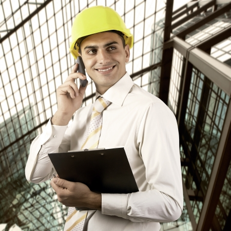 Young architect wearing a protective helmet standing on the building outdoor background Stock Photo - 18498838