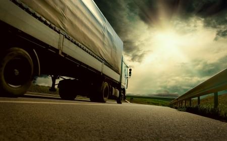 transporte: Hermosa vista con truckcar en la carretera bajo el cielo con las nubes