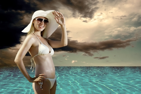 Beautiful happiness girl in white hat on ther beach photo