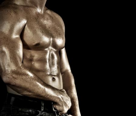 Bodybuilder posing on the black background photo