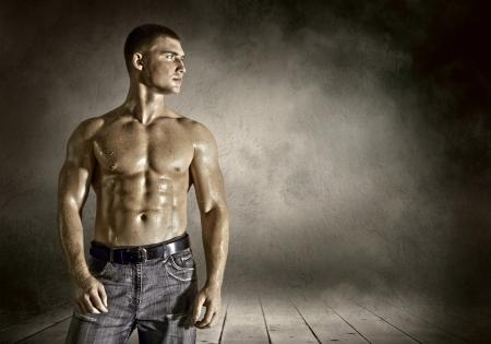 Bodybuilder posing on the outdoor grunge background photo