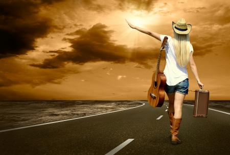 woman guitar: Young woman with guitar on the road and her vintage baggage