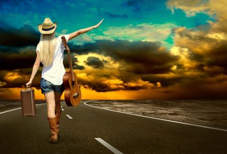 country: Jonge vrouw met gitaar op de weg en haar vintage bagage