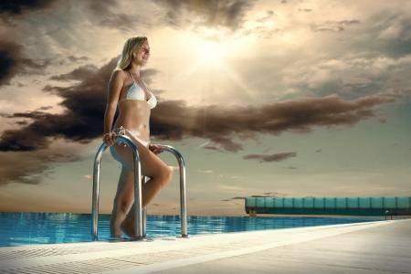 Beautiful happiness girl in white bikini stay near the waterpool Stock Photo