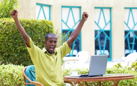 Young happy man or student with laptop sitting at the table  photo